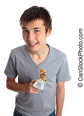 Smiling boy holding muesli bar