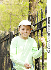 Smiling boy holding on to fence
