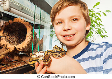 Smiling boy holding Royal python in his hands - Close-up...