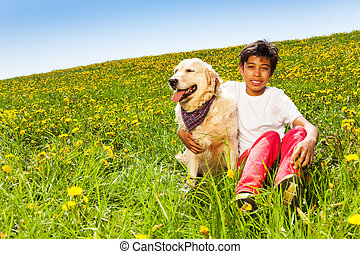 Smiling boy hugs cute dog sitting on green grass