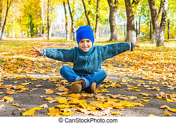 smiling boy in a hat and sweater sitting in the Park in the autumn