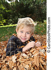 Smiling boy in a pile of leaves