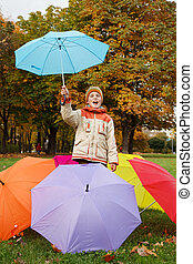 Smiling boy in autumn park. In environment of multi-coloured umbrellas.
