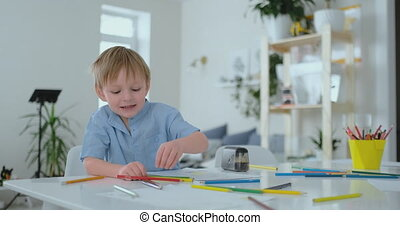 Smiling boy in blue shirt draws on paper with a pencil while...