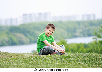 Smiling boy in casual on grass