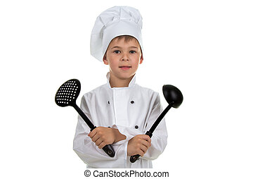 Smiling boy in chef uniform holding kitchen equipment, on white background.