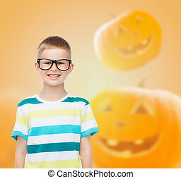 smiling boy in glasses over pumpkins background