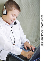Smiling boy in headset working on laptop