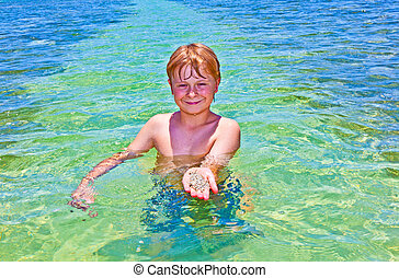 boy in the ocean shows clean sand on his hand