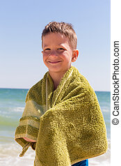 Smiling boy in the towel on beach