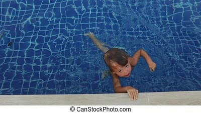 Smiling boy in water near edge of pool - From above cheerful...