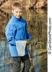 Smiling boy in winter clothes with fishing net