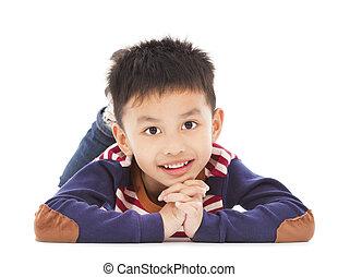 smiling boy is lying on the floor