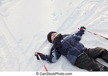 Smiling boy laying down on snow