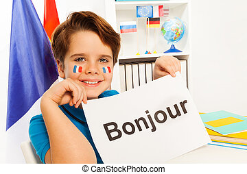 Smiling boy learning French at the classroom