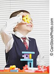 Smiling boy looking through toy block