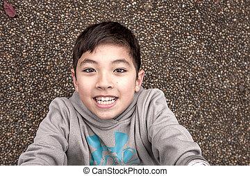Smiling boy looking up at camera.