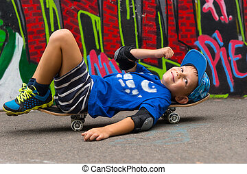 Smiling Boy Lying on Skateboard in Urban Park