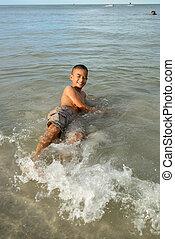 smiling boy lying on the beach