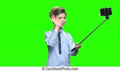 Smiling boy making photos using selfie stick.