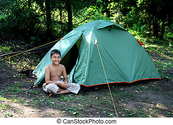 smiling boy near camping tent