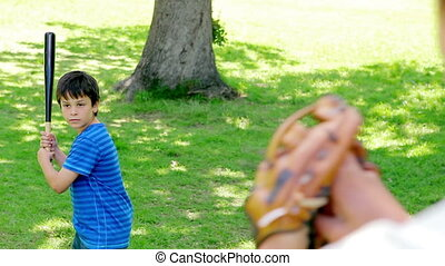 Smiling boy playing baseball with his father