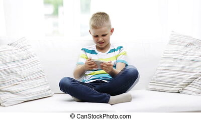 smiling boy playing with smartphone at home