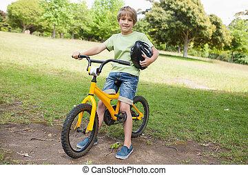 Smiling boy riding bicycle at park