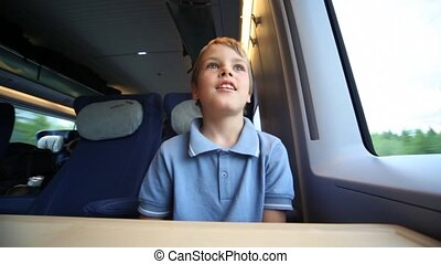 Smiling boy sits and looks out of window train during movement