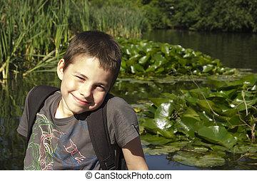 smiling boy sitting at lake in summer