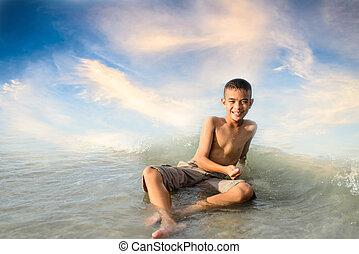 smiling boy sitting on the beach