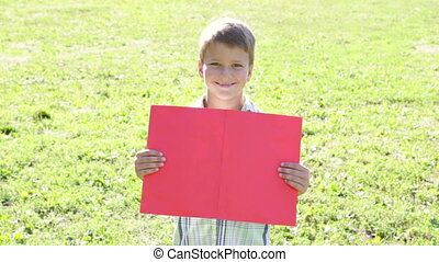 Smiling boy standing with empty blank banner in hands,...