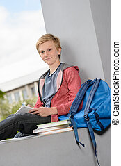 Smiling boy studying sitting on school wall