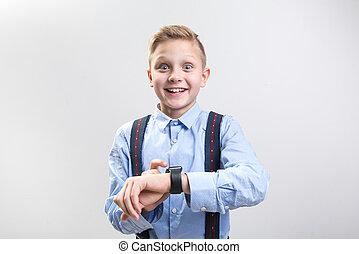 Smiling boy taking delight in new wristwatch