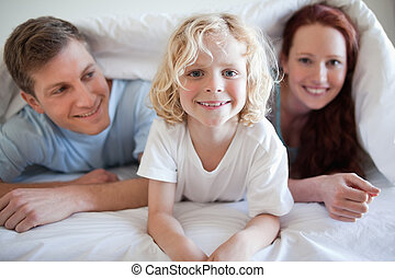 Smiling boy under the cover with his parents