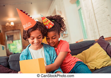 Smiling boy unwrapping his birthday present with his friend