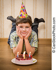 Smiling boy with birthday cake on the floor