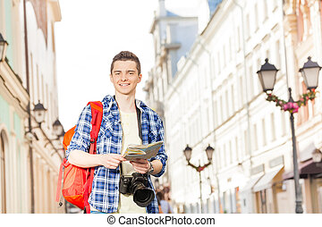 Smiling boy with camera and city map on the street