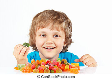 Smiling boy with candies on white background
