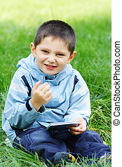 Smiling boy with closed book