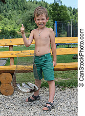 Smiling boy with freshly caught fish in summer