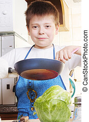 Smiling boy with frying-pan