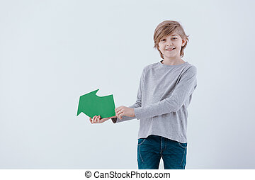 Smiling boy with green arrow
