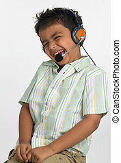 smiling boy with headphones - a smiling Asian boy of indian...