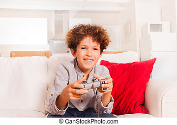 Smiling boy with joystick playing video games