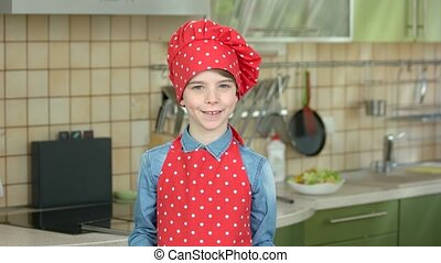 Smiling boy with kitchen utensils. Happy kid in chef...