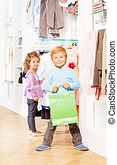 Smiling boy with shopping bag and girl behind