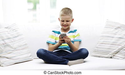 smiling boy with smartphone at home - home, leisure,...