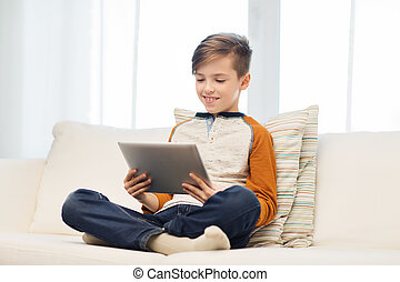 smiling boy with tablet computer at home