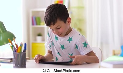 smiling boy with tablet pc sitting at home desk - childhood,...